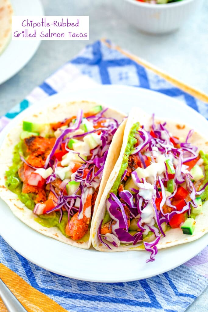 Overhead view of a white plate with two fully loaded chipotle-rubbed grilled salmon tacos with red cabbage, apple cucumber salsa, guacamole, and mayo drizzle with recipe title at top