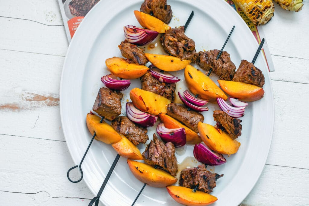 Landscape bird's eye view of chipotle steak and peach kabobs with red onion on white platter