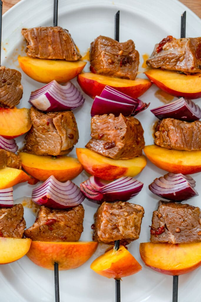 Overhead view of steak and peach kabobs on platter ready to be grilled