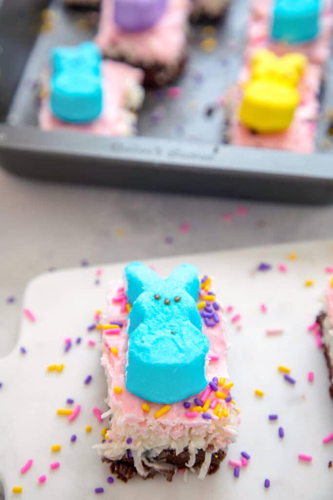 Overhead view of a chocolate coconut brownie bar with pink icing and a blue Peep on top with lots of sprinkles and a pan of more Peeps bars in the background