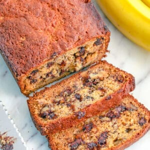 Overhead closeup view of a loaf of chocolate chip banana bread with a couple slices cut a knife and bananas in the background.