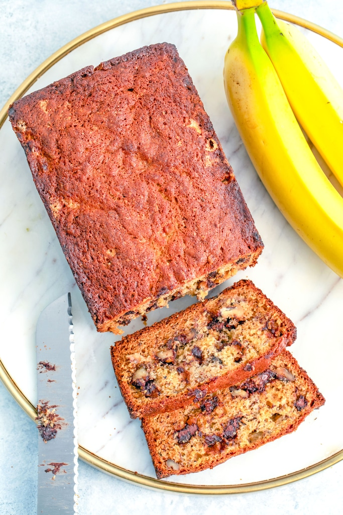 Bird's eye view of a loaf of chocolate chip banana bread with slices cut out on a marble tray with knife and bananas in background.