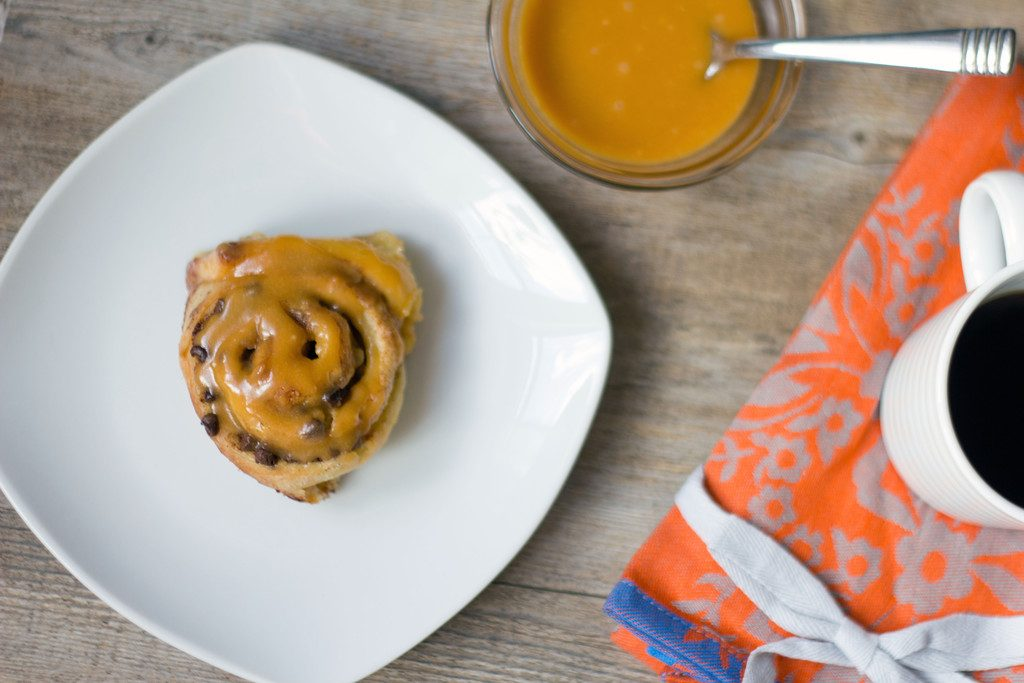 Landscape view of a chocolate chip cinnamon roll with butterscotch icing on a white plate with bowl of butterscotch icing and cup of coffee on an orange tea towel in the background