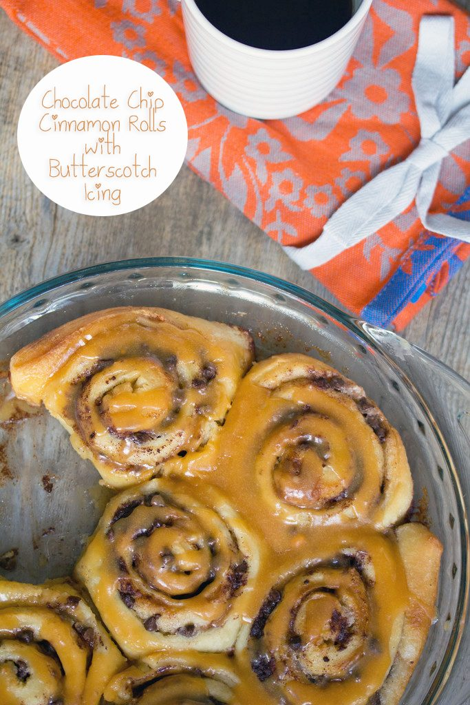 Overhead view of a dish of chocolate chip cinnamon rolls with butterscotch icing drizzled over the top and a cup of coffee on a tea towel in the background with recipe title at top