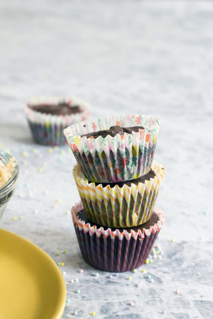 Head-on view of three chocolate chip cookie dough cups in spring baking papers stacked on top of each other on marble surface