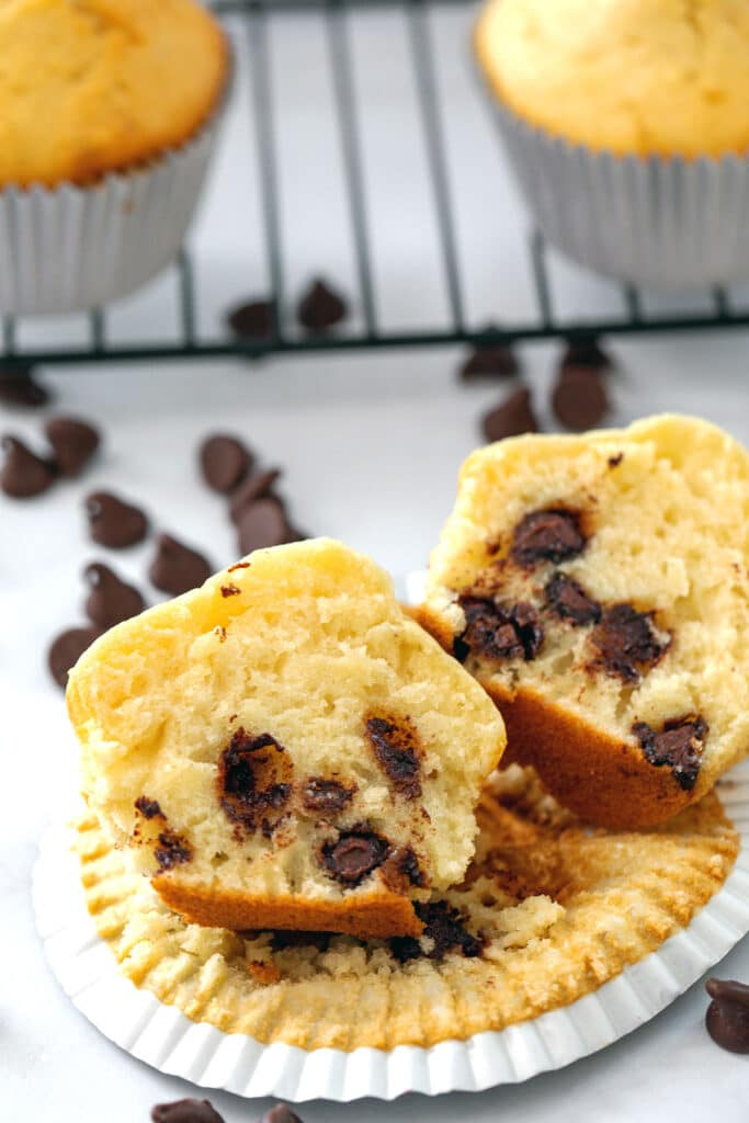 Two halves of a chocolate chip muffin with pancake mix with a rack of more muffins and chocolate chips in background