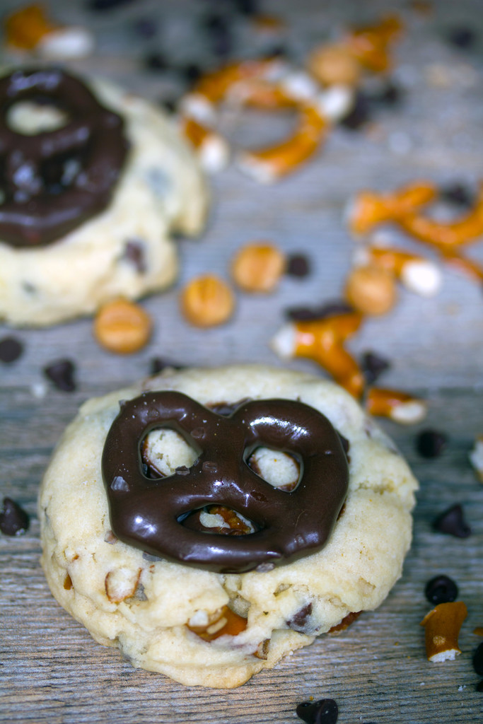 Two cookies topped with chocolate-covered pretzels with caramel bits, chocolate chips, and pretzel pieces in the background