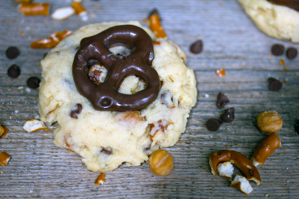 Landscape photo of cookie topped with chocolate-covered pretzel and caramel bits, pretzel pieces, and chocolate chips scattered in the background