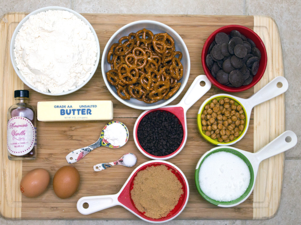 Overhead photo of the ingredients for the cookies on a cutting board, including pretzels, chocolate chips, eggs, butter, flour, caramel bits, sugar, vanilla, baking powder, salt, brown sugar, and chocolate melting wafers
