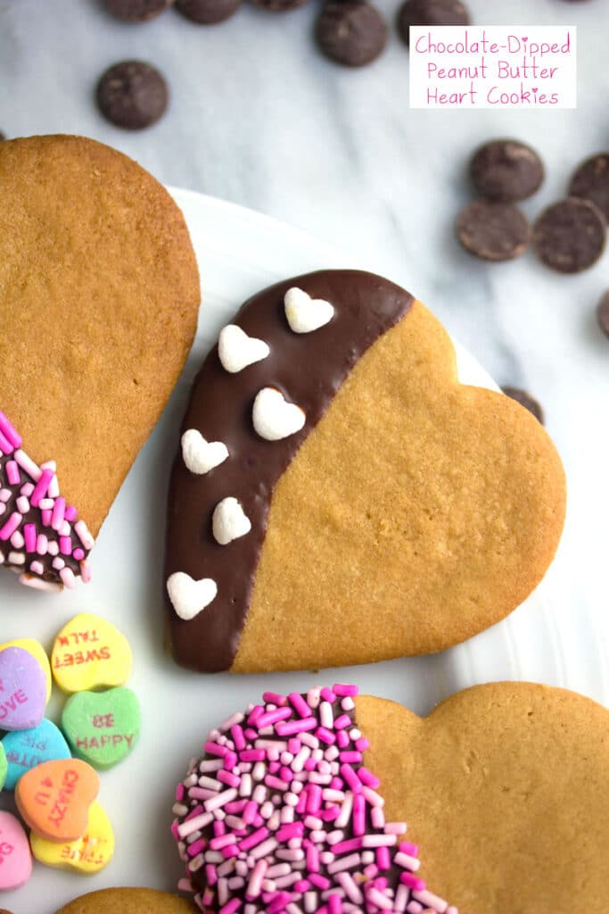 Overhead view of chocolate-dipped peanut butter heart cookies on a plate with sprinkles and mini heart marshmallows and conversation hearts with recipe title at top