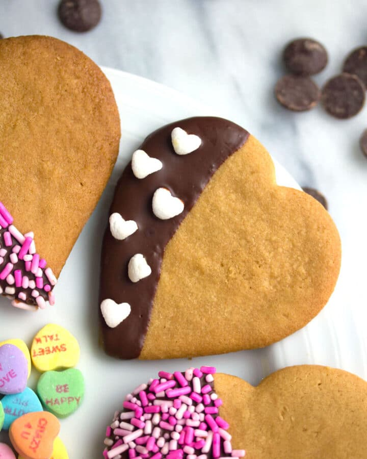 Overhead view of chocolate-dipped peanut butter heart cookies on a plate with sprinkles and mini heart marshmallows and conversation hearts