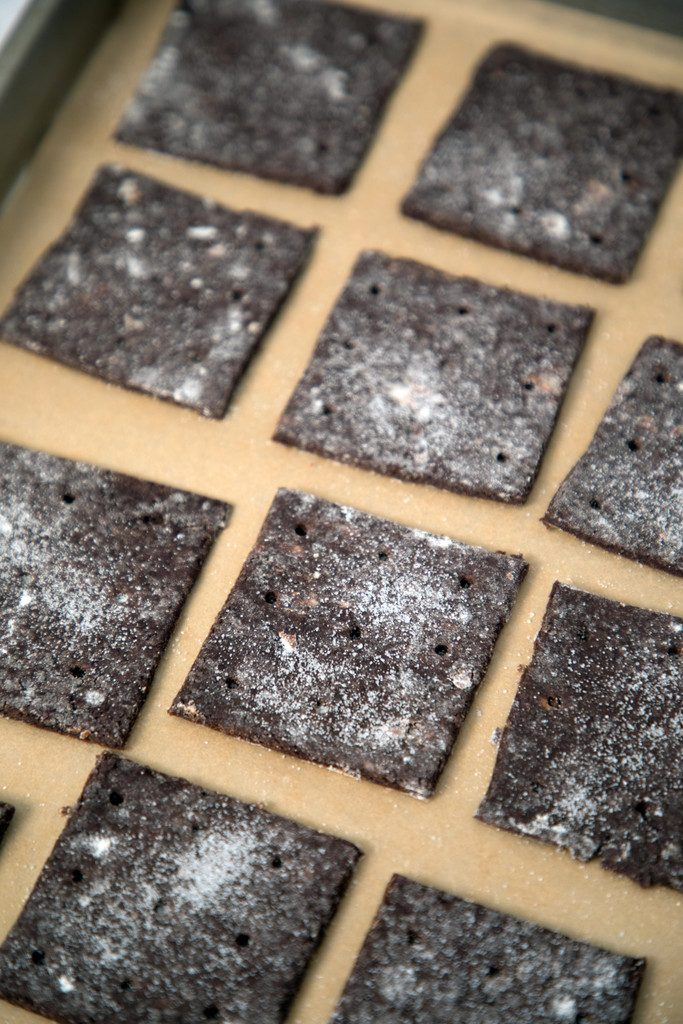 Overhead view of chocolate graham cracker dough sliced into squares on baking sheet ready for oven