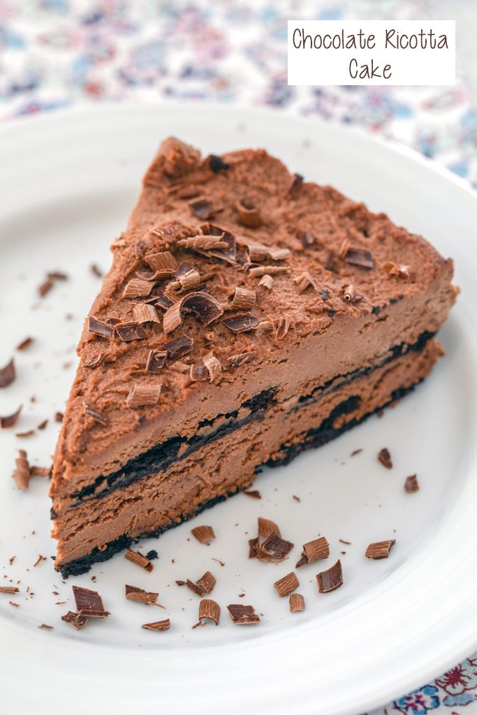 Overhead view of a slice of chocolate ricotta cake on a white plate topped with chocolate shavings with recipe title on top