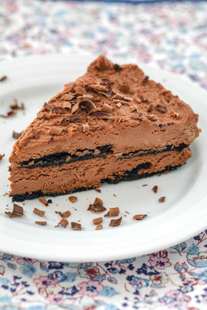 Head-on view of a slice of chocolate ricotta cake on a white plate topped with chocolate shavings