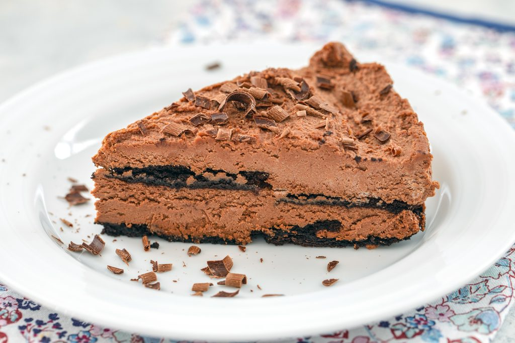 Landscape head-on view of a slice of chocolate ricotta cake topped with chocolate shavings