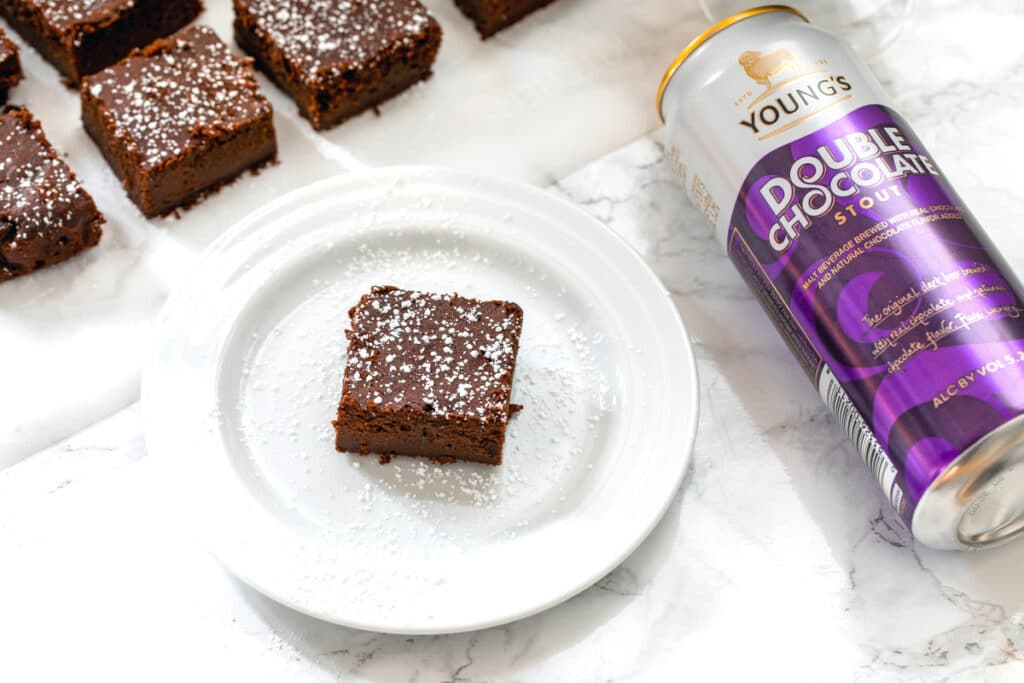 Landscape overhead photo of chocolate stout brownie with can of Young's Double Chocolate Stout and more brownies lined up in background