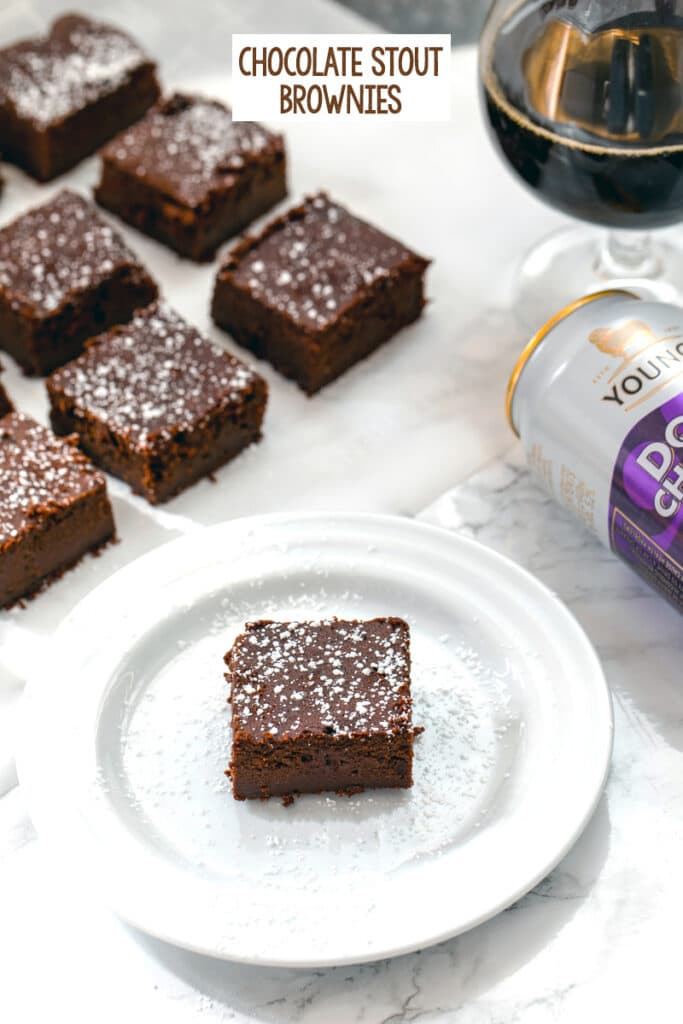 Head-on view of a chocolate stout brownie on a white plate with more brownies, can of chocolate stout, and glass of chocolate stout in background with recipe title at top of image