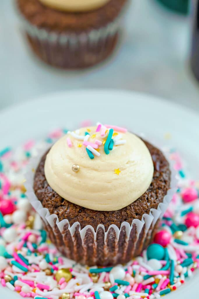 Overhead view of chocolate stout cupcake with Baileys frosting and sprinkles on a white plate covered in sprinkles