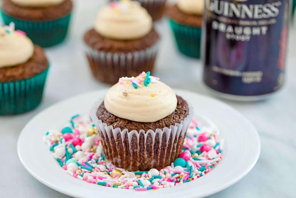 Landscape view of chocolate stout cupcake with Baileys frosting and sprinkles on a white plate covered in sprinkles with more cupcakes and can of Guinness in the background