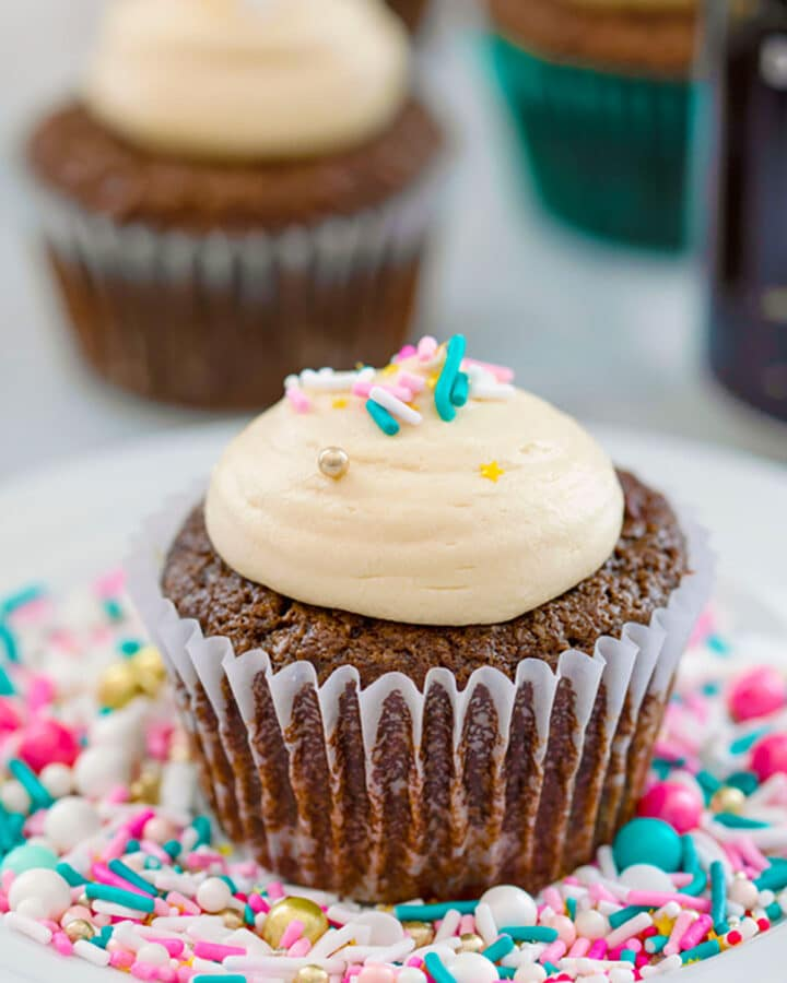 Head-on view of a chocolate stout cupcake with Baileys frosting and sprinkles on top sitting on a bed of sprinkles
