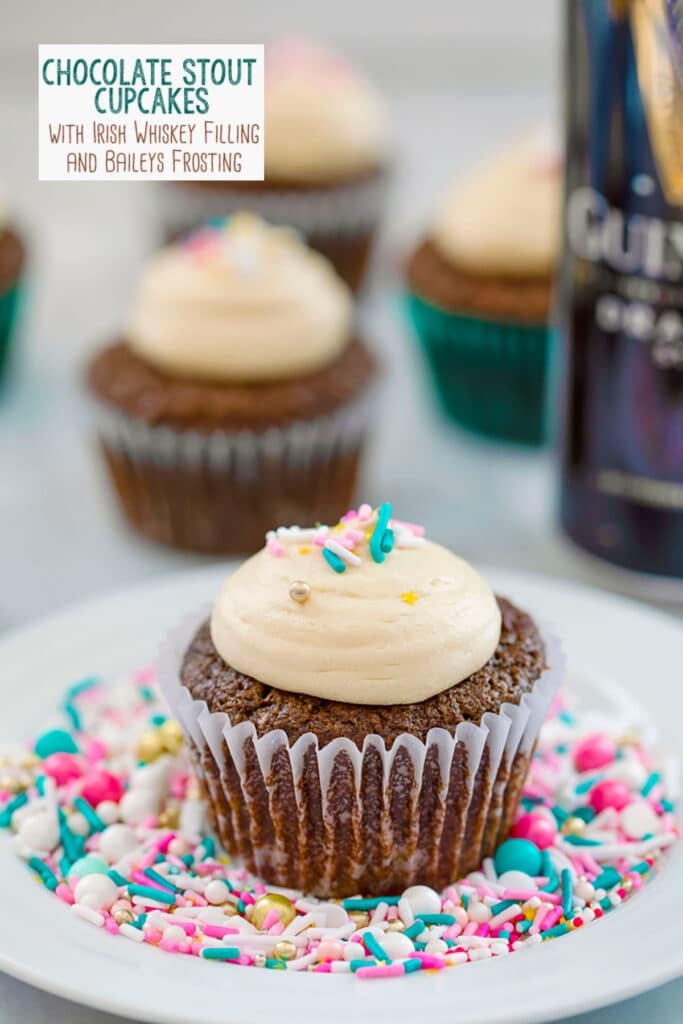 Head-on view of a chocolate stout cupcake with Baileys frosting and sprinkles on a white plate covered in sprinkles with more cupcakes and can of Guinness in the background and recipe title at top