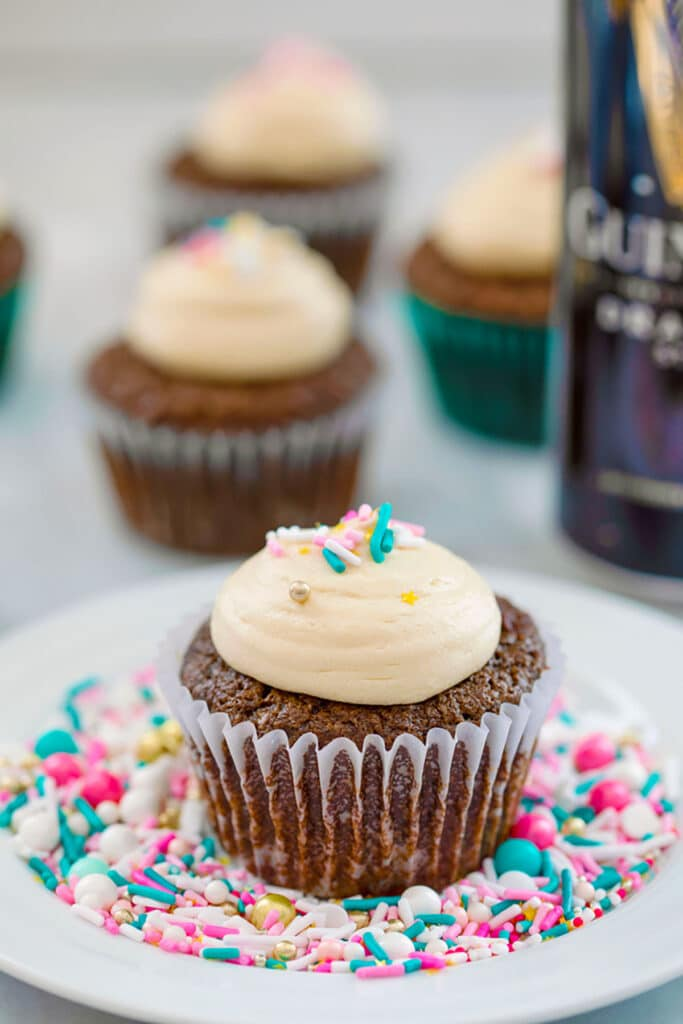 Head-on view of a chocolate stout cupcake with Baileys frosting and sprinkles on a white plate covered in sprinkles with more cupcakes and can of Guinness in the background