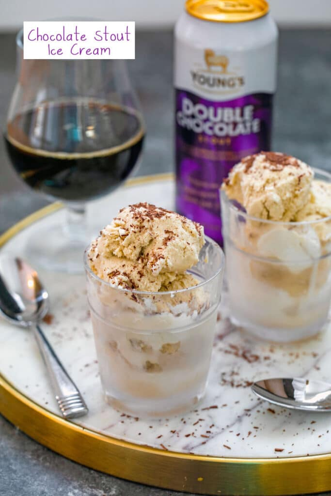 Head-on view of two clear glasses with chocolate stout ice cream on a marble tray with chocolate shavings, spoon, glass of beer and can of chocolate stout with recipe title at top