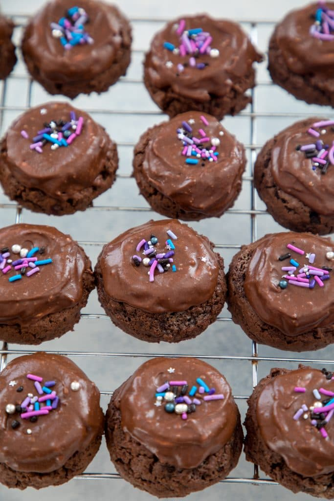 Baking rack filled with chocolate surprise cookies topped with pink and purple sprinkles