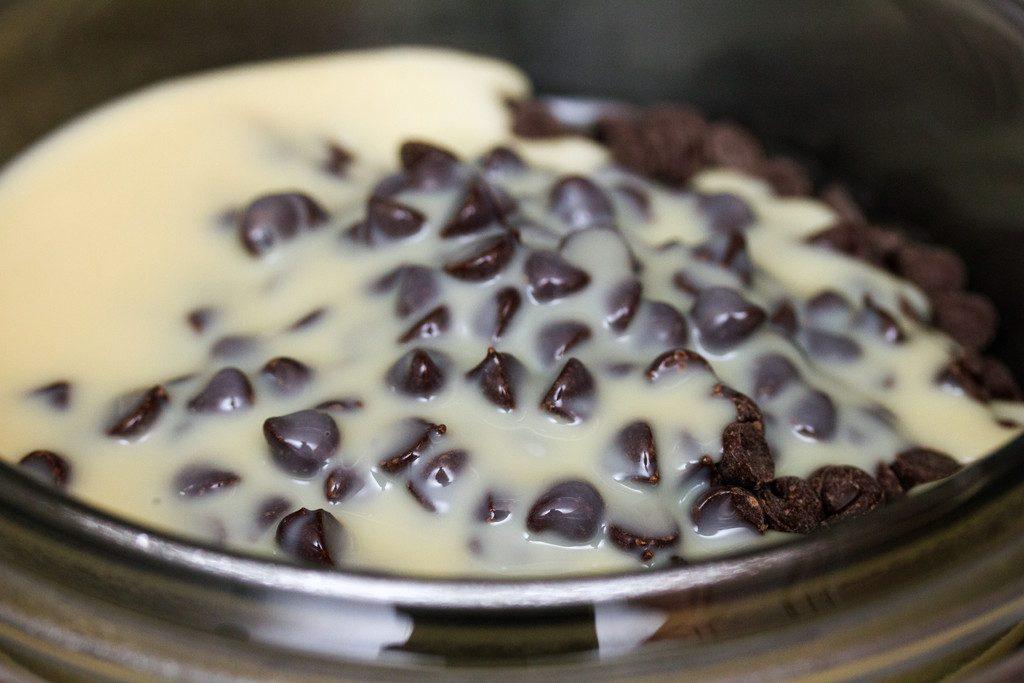 Condensed Milk and chocolate chips being heated to make chocolate fudge