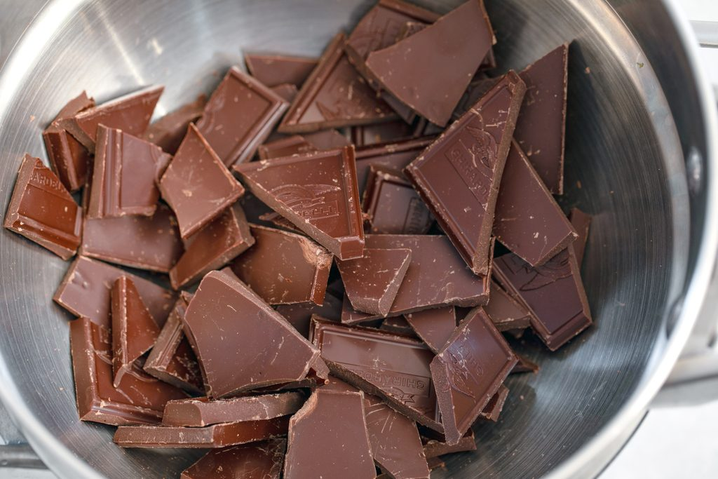 Overhead view of a double boiler with chopped chocolate in it