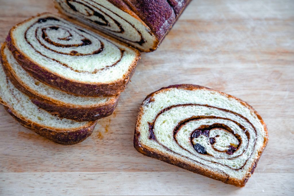 Landscape view of loaf of cinnamon raisin bread with slices taken out sitting on a cutting board