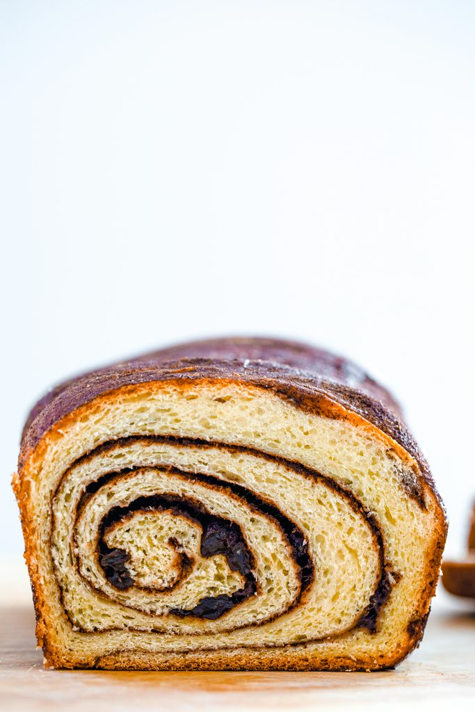 Head-on view of a loaf of cinnamon raisin bread showing the perfect cinnamon swirl with recipe title at top of image