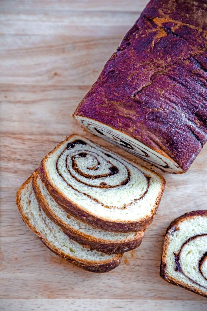 Overhead view of a loaf of cinnamon raisin bread on a cutting board with slices cut out of it