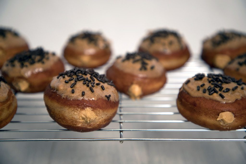 Cinnamon Peanut Butter Doughnuts -- Deliciously fried donuts filled with peanut butter cream and topped with a cinnamon peanut butter glaze | wearenotmartha.com