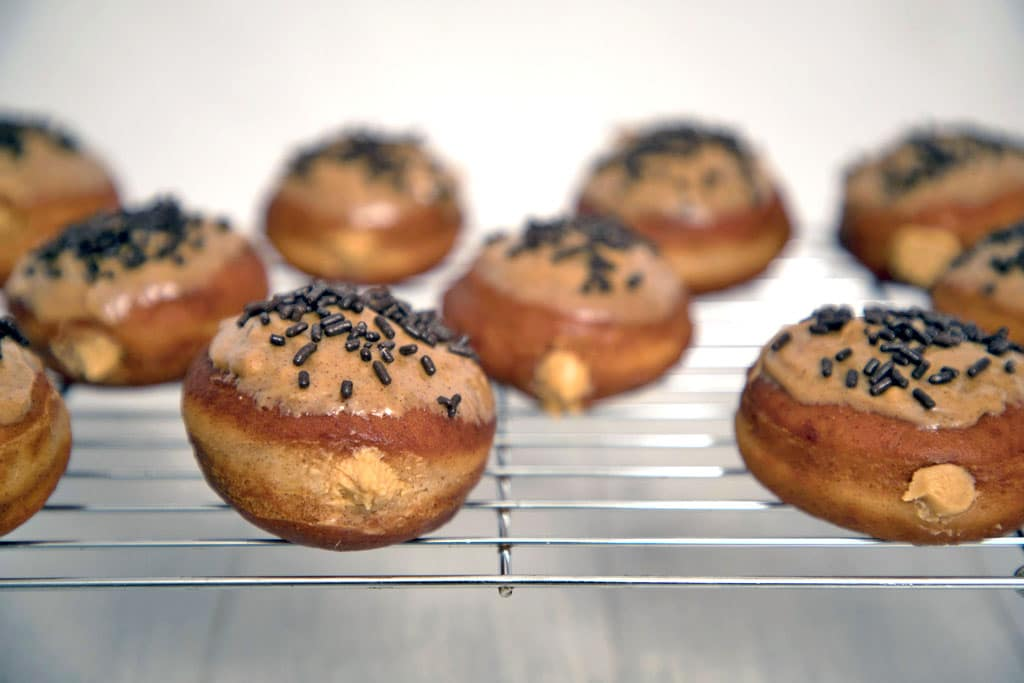 Landscape view of multiple peanut butter doughnuts on baking rack al topped with cinnamon peanut butter glaze and chocolate sprinkles with peanut butter cream filling peeping out.