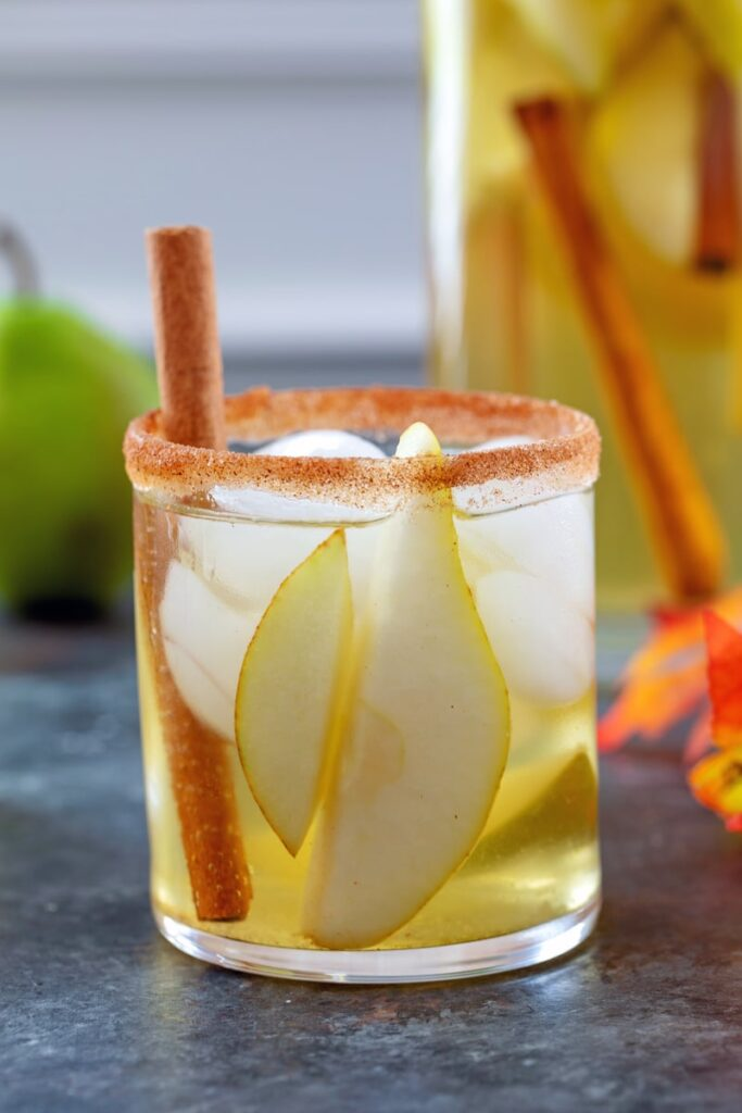 Head-on closeup view of a cinnamon sugar rimmed glass of cinnamon pear sangria with cinnamon stick garnish