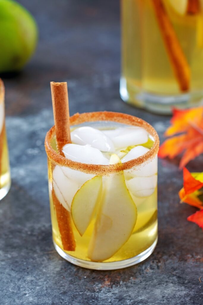 Glass of cinnamon pear sangria with fall leaves and pitcher of sangria in background