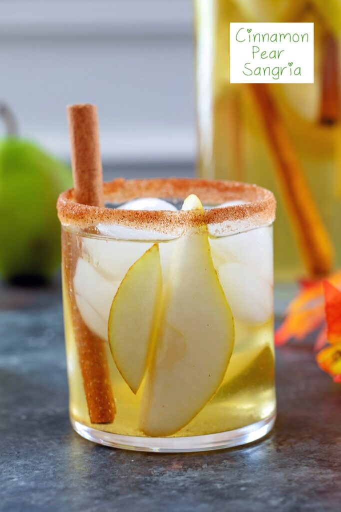 Head-on closeup view of a cinnamon sugar rimmed glass of cinnamon pear sangria with cinnamon stick garnish and recipe title at top