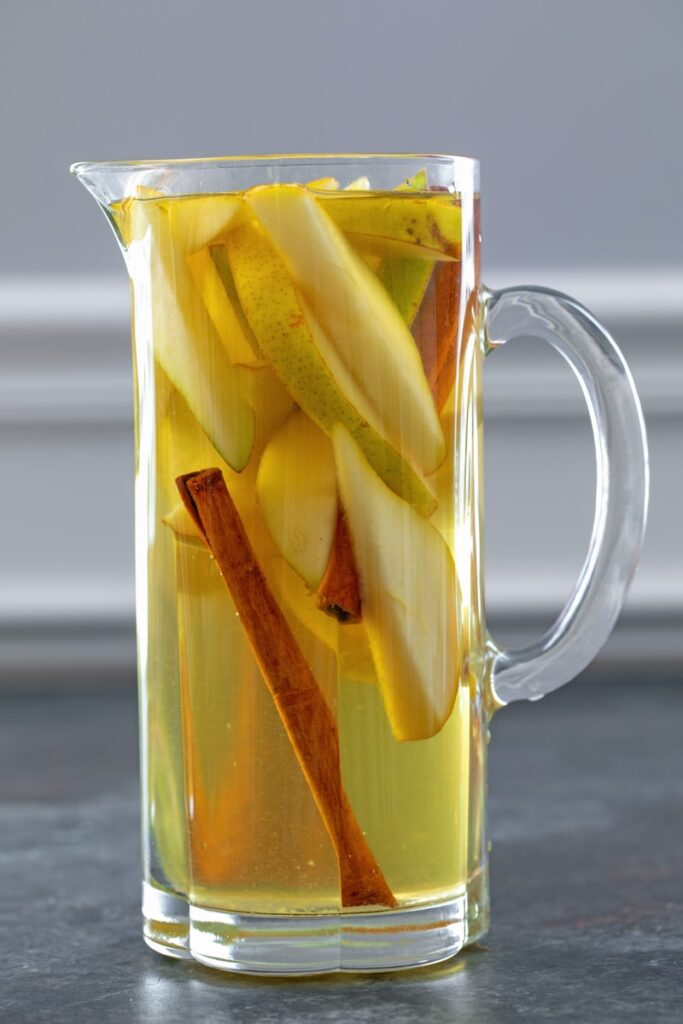 Head-on closeup view of pitcher of sangria with sliced pears and cinnamon sticks