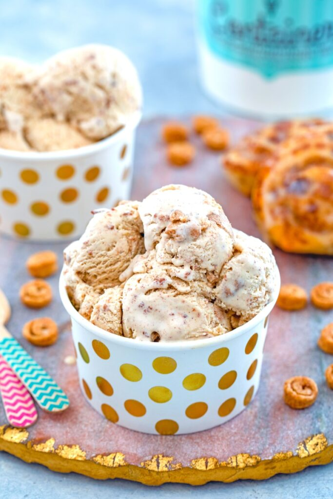 View of a small cup of cinnamon roll ice cream with mini cinnamon rolls, large cinnamon rolls, second cup of ice cream, and ice cream quart container in background with recipe title at top