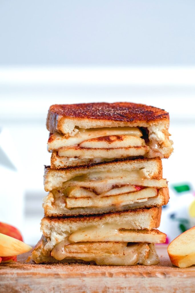 Cinnamon sugar brie and apple grilled cheese sandwich halves stacked on top of each other with apples in background and recipe title at top