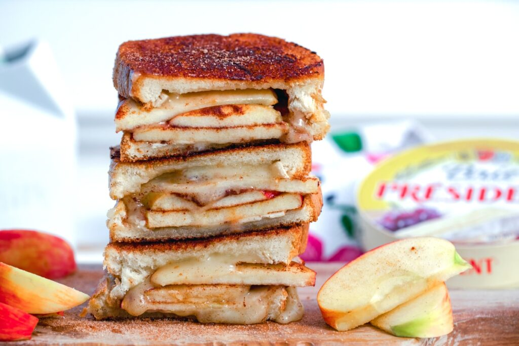 Landscape view of cinnamon sugar brie and apple grilled cheese halves stacked on top of each other with apples and brie package in background