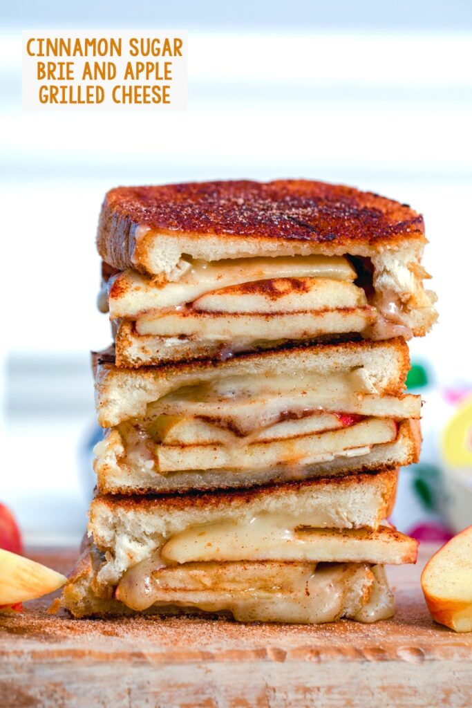 Close-up of cinnamon sugar brie and apple grilled cheese sandwich halves stacked on top of each other with apples in background and recipe title at top