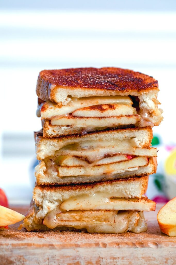 Close-up of cinnamon sugar brie and apple grilled cheese sandwich halves stacked on top of each other with apples in background
