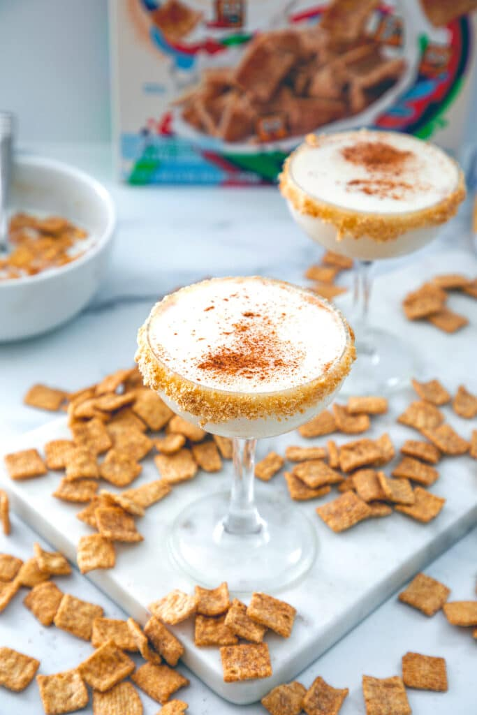 Overhead view of two Cinnamon Toast Crunch cocktails with cereal all around, bowl of cereal and milk and cereal box in the background
