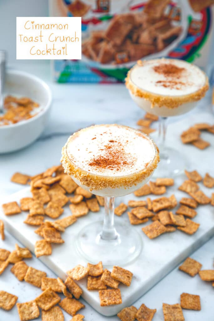 Overhead view of two Cinnamon Toast Crunch cocktails with cereal all around, bowl of cereal and milk and cereal box in the background with recipe title at top