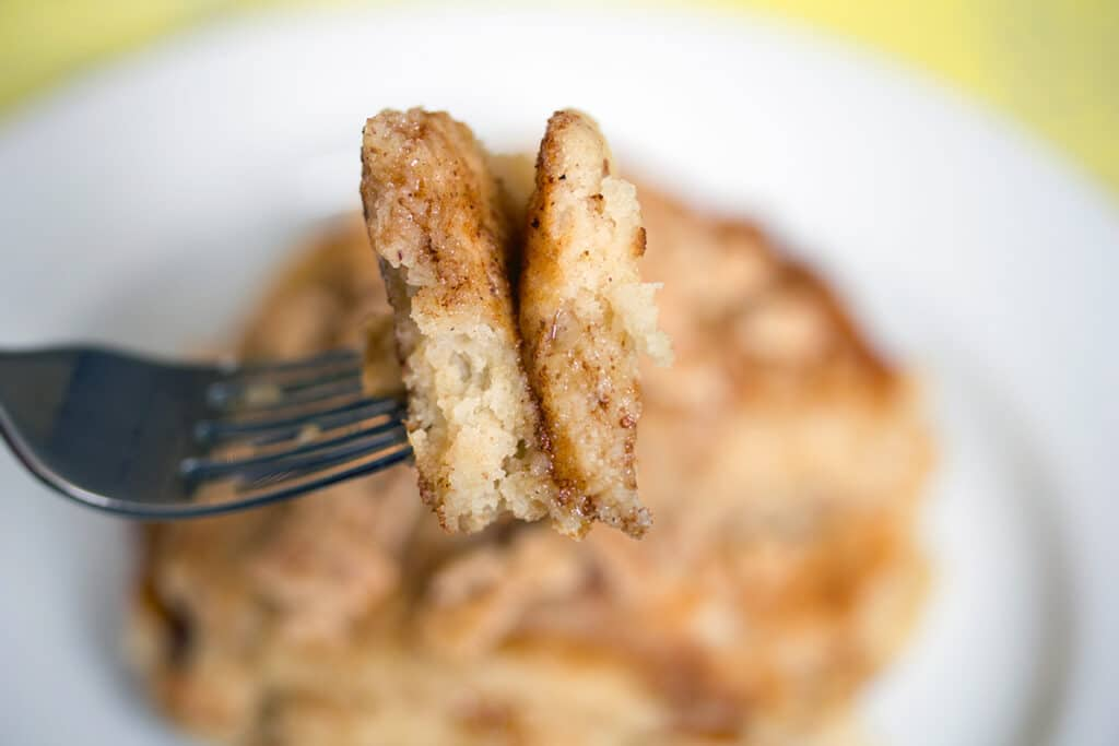 Landscape close-up view of a fork holding up two bites of Cinnamon Toast Crunch pancakes