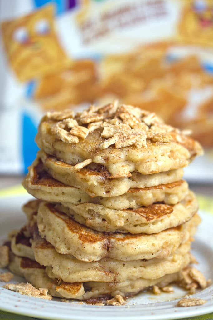 Head-on view of a big stack of cinnamon toast crunch pancakes with crushed Cinnamon Toast Crunch cereal on top and cereal box in the background