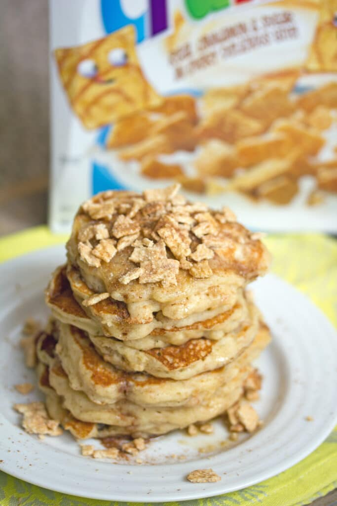 Overhead view of a stack of Cinnamon Toast Crunch pancakes with cereal crushed over the top on a white plate with cereal box in the background