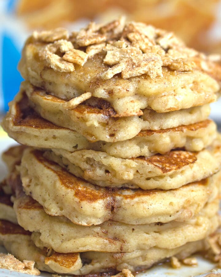 Head-on closeup view of a stack of cinnamon toast crunch pancakes with crushed Cinnamon Toast Crunch cereal on top